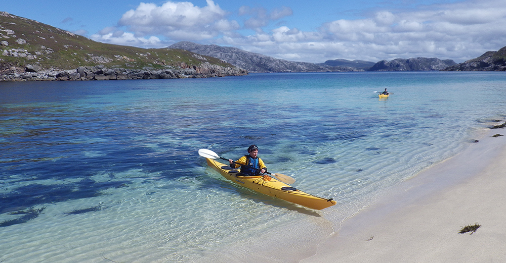 Sea kayaking in the Outer Hebrides, Scotland with white sandy beaches and crystal clear water. Photo used with permission of Wilderness Scotland
